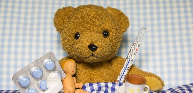 Teddy bear in bed with some tablets, a tissue and a cup